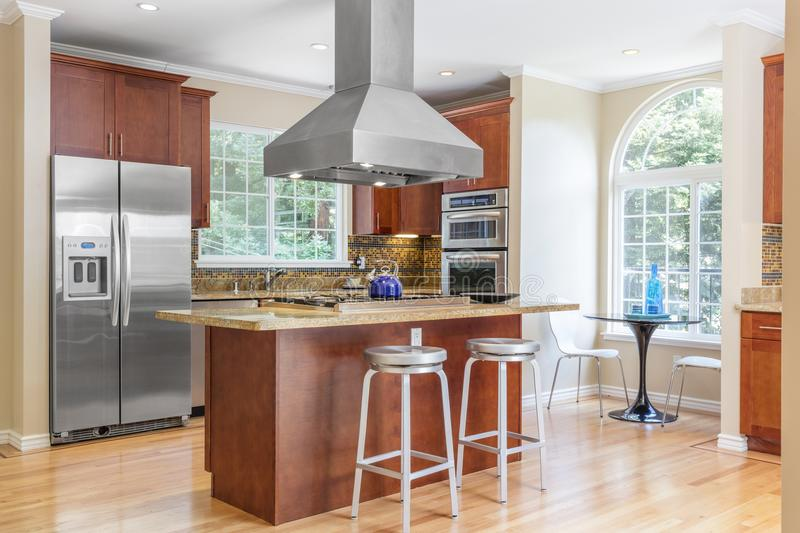 Kitchen in luxury home with stainless steel appliances. Wooden Kitchen in luxury home with, kitchen island, stainless steel appliances, granite work surfaces stock photo
