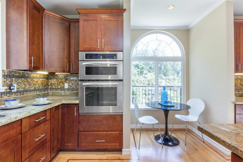 Kitchen in luxury home with stainless steel appliances,. Wooden Kitchen in luxury home, with kitchen island, stainless steel appliances, granite work surfaces royalty free stock photography