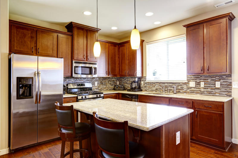 Kitchen mahogany storage combination with steel kitchen appliances and back splash trim. Kitchen mahogany storage combination with steel kitchen appliances royalty free stock images