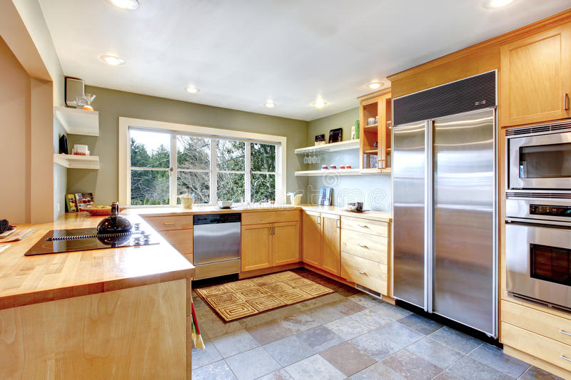 Kitchen with maple cabinets and steel appliances. Kitchen with concrete floor and french window. Maple cabinets blend perfectly with stainless steel appliances royalty free stock images