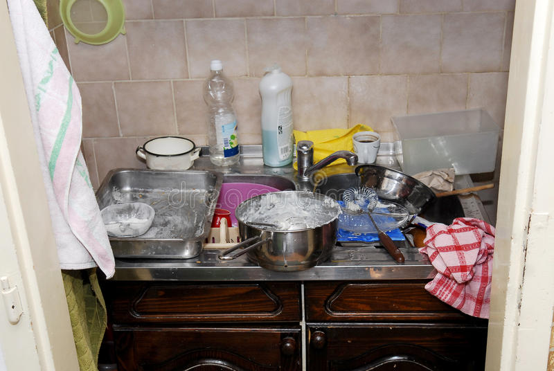Kitchen in a mess. Pile of dirty dishes in the kitchen royalty free stock photography