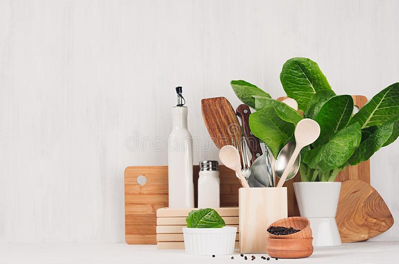 Kitchen modern decor - beige wooden utensils, brown cutting boards, green plant on soft light white wood background. stock images