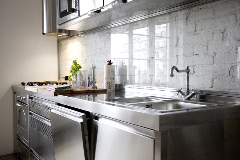 Modern Kitchen with Stainless Steel Appliances. Stainless steel appliances in a new modern kitchen with a white brick wall stock photos