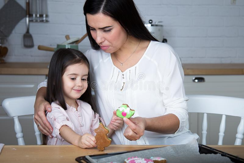 In the kitchen, mom and daughter bake cookies. Mom and little daughter bake Christmas cookies in the kitchen stock photo