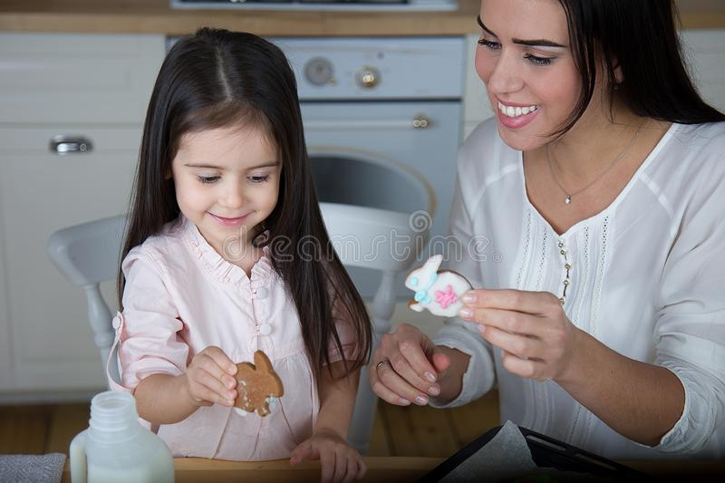 In the kitchen, mom and daughter bake cookies. Mom and little daughter bake Christmas cookies in the kitchen royalty free stock photos