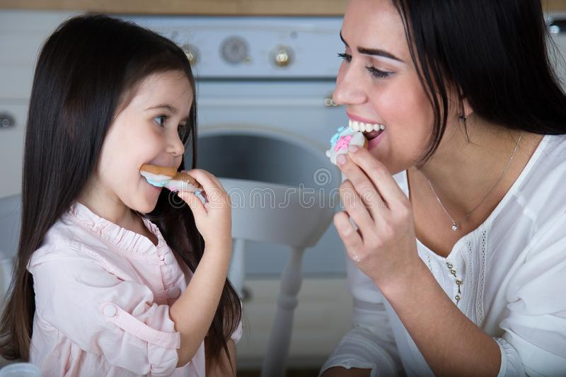 In the kitchen, mom and daughter bake cookies. Mom and little daughter bake Christmas cookies in the kitchen royalty free stock photography