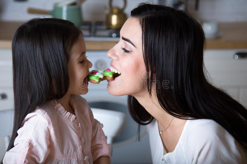 In the kitchen, mom and daughter bake cookies. Mom and little daughter bake Christmas cookies in the kitchen royalty free stock image