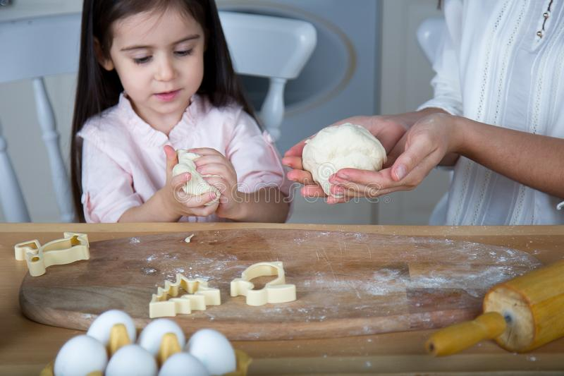 In the kitchen, mom and daughter bake cookies. Mom and daughter bake cookies. On the kitchen table are eggs,milk, dough royalty free stock images