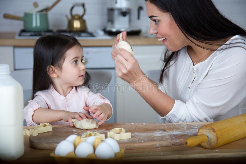 In the kitchen, mom and daughter bake cookies. Mom and daughter bake cookies. On the kitchen table are eggs,milk, dough stock image