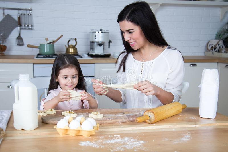 In the kitchen, mom and daughter bake cookies. Mom and daughter bake cookies. On the kitchen table are eggs,milk, dough royalty free stock photography