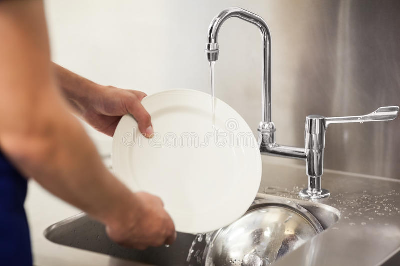 Kitchen porter cleaning white plates in sink. In professional kitchen royalty free stock images