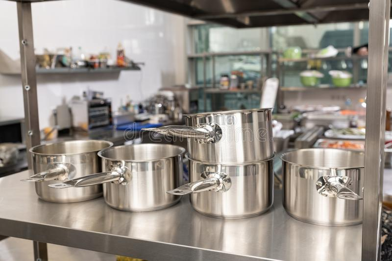 kitchen pots, grater, bowls, saucepans stacked up on a shelf in a kitchen; restaurant / commercial or home kitchen. Brick wall in royalty free stock photos