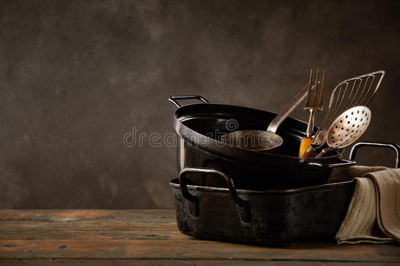 Kitchen pots and utensils on wooden countertop royalty free stock photography