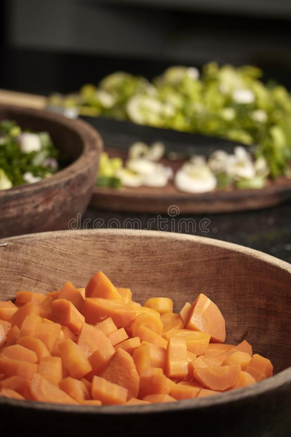 Raw vegetables of green and orange color. Kitchen. Raw vegetables of green color. Nutritious and delicious food. Woman cutting green onion, zucchini, carrots royalty free stock photo