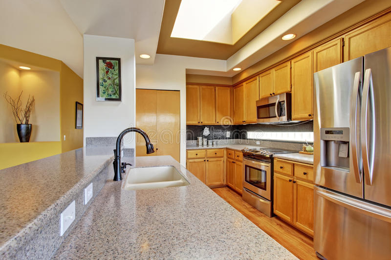 Kitchen room with steel appliances and granite tops. Bright kitchen room with skylight, steel appliances and granite tops stock image