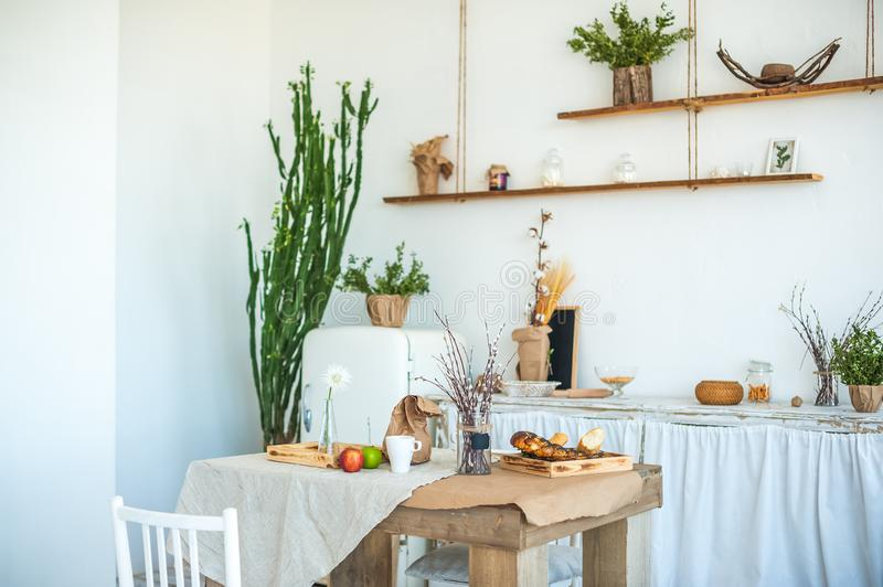 Kitchen in rustic style in summer. Spring light textured kitchen with an old fridge, wooden table. A wooden tray with a vase, will. Ows, a white cup, a green and stock photography