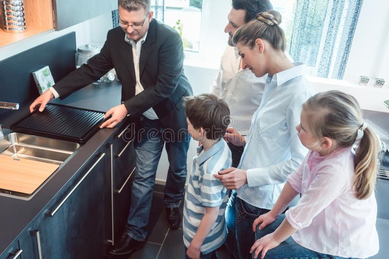 Kitchen sales with a family, kids, and a service expert stock photos