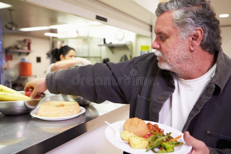 Kitchen Serving Food In Homeless Shelter. Kitchen Serving Hot Food In Homeless Shelter With Man Picking Up Fruit stock images