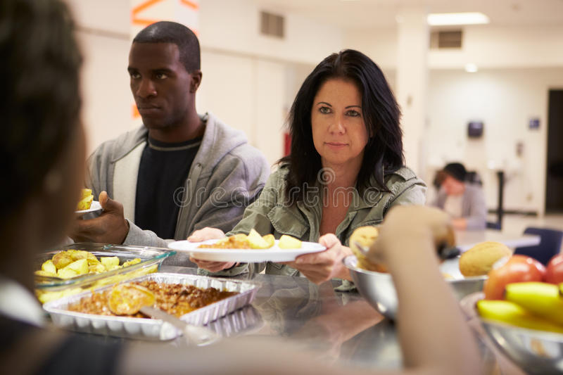 Kitchen Serving Food In Homeless Shelter. Kitchen Serving Hot Food In Homeless Shelter To Male And Female royalty free stock image