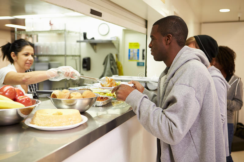 Kitchen Serving Food In Homeless Shelter. Kitchen Serving Hot Food In Homeless Shelter To Male And Females royalty free stock photo