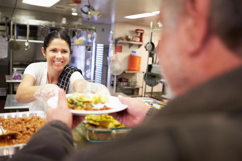 Kitchen Serving Food In Homeless Shelter. Kitchen Serving Hot Food In Homeless Shelter To Man stock photos