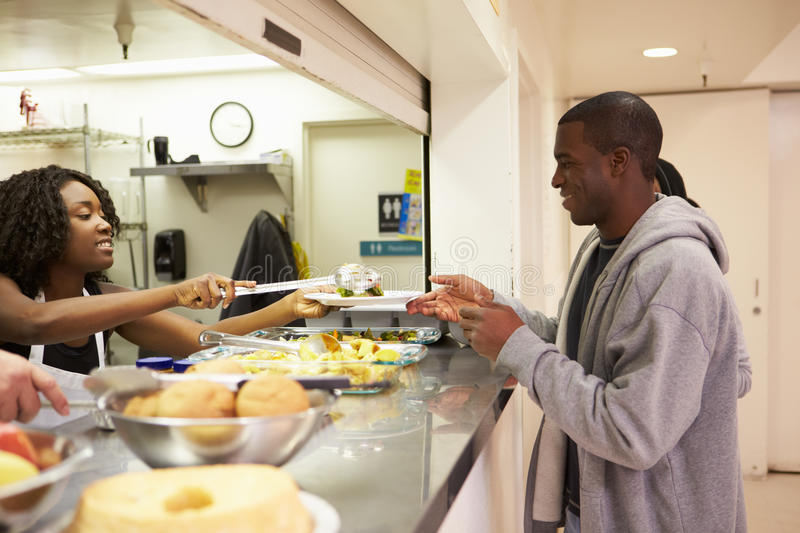 Kitchen Serving Food In Homeless Shelter. Kitchen Serving Hot Food In Homeless Shelter To Man Smiling royalty free stock images