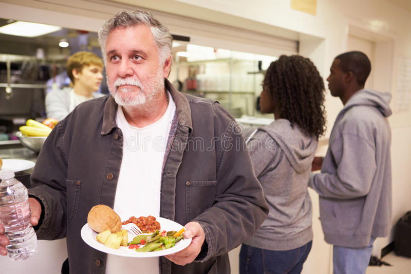 Kitchen Serving Food In Homeless Shelter. With Man Holding Water Bottle And Plate Of Food royalty free stock image
