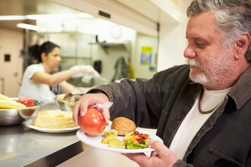 Kitchen Serving Food In Homeless Shelter. With Man Putting Apple On Plate royalty free stock images