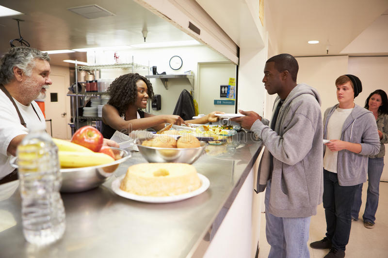 Kitchen Serving Food In Homeless Shelter. To Hungry People stock photos