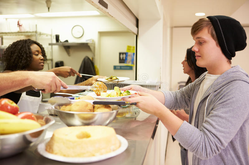 Kitchen Serving Food In Homeless Shelter. To Hungry Poor People royalty free stock photo
