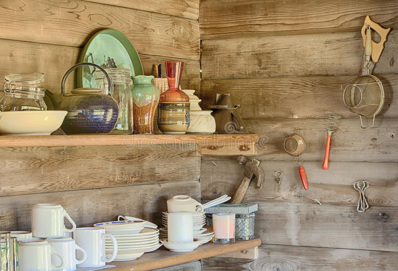 Kitchen Shelves. A still life image of kitchecn shelves in an old log cabin showing the plates, cups, bowls and other houswares arranged on each shelf royalty free stock image