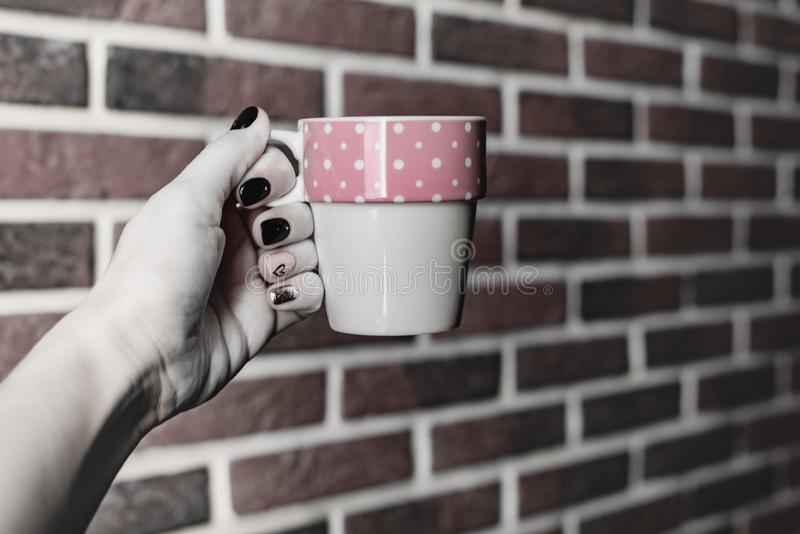 Kitchen still life, female hand with beautiful manicure holds a mug of pink white isolated on a background of an old red brick wal royalty free stock photo