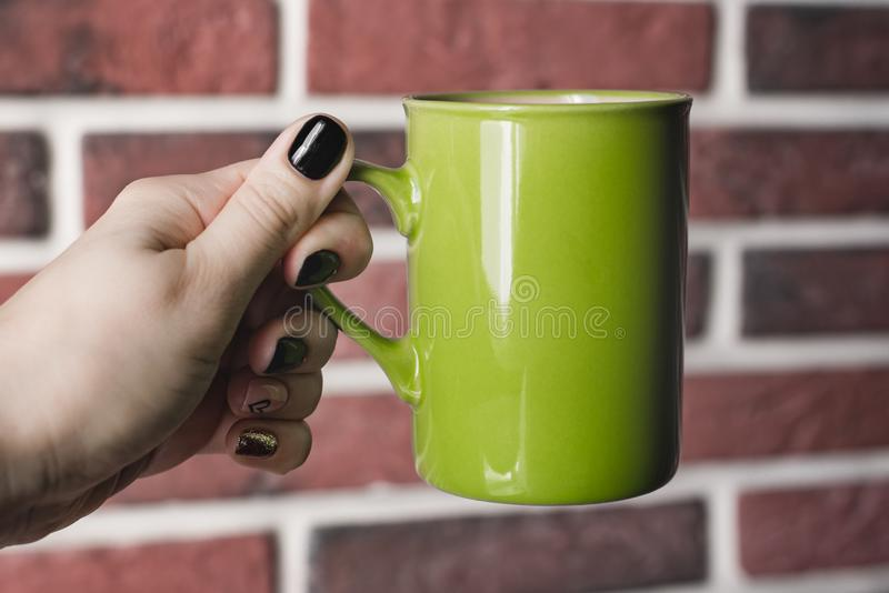 Kitchen still life, female hand with beautiful manicure holds a mug of pink white isolated on a background of an old red brick wal stock photo