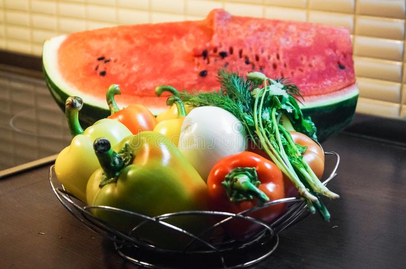 Kitchen still life. Fresh raw sweet peppers with onion and verdure and water melon. stock photos