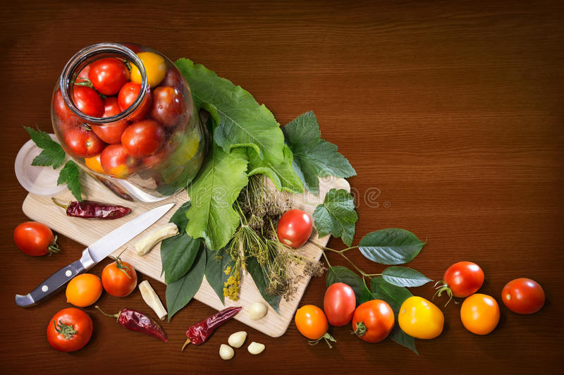 Kitchen still life of objects cooking pickled tomatoes. Different varieties of fresh ripe tomatoes arranged in glass jar, knife, leaves, tufts of dry fennel stock images