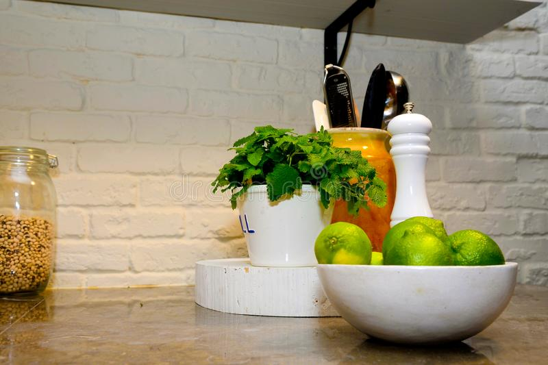 Kitchen Stone Counter with Limes, Peppermint, Pepper Mill, Healthy. Modern kitchen corner with white bricks on the wall and granite counter. White ceramic bowl stock photo