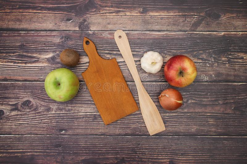 Kitchen supplies and onions and apples on table.  royalty free stock images