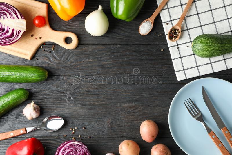 Kitchen supplies, vegetables and spices on wooden background. Copy space stock images