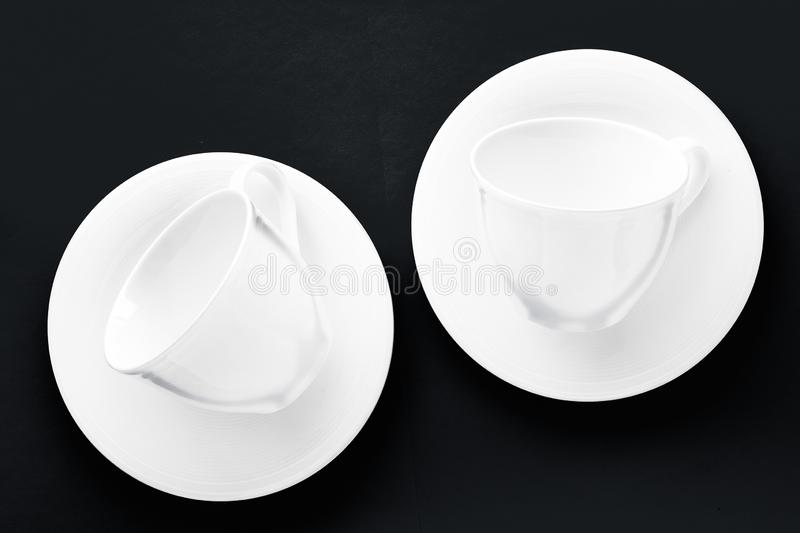 White tableware crockery set, empty cup on black flatlay background. Kitchen, table decor and drinks menu concept - White tableware crockery set, empty cup on royalty free stock photos