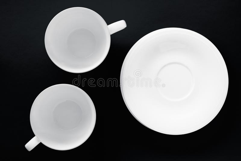 White tableware crockery set, empty cup on black flatlay background. Kitchen, table decor and drinks menu concept - White tableware crockery set, empty cup on royalty free stock image