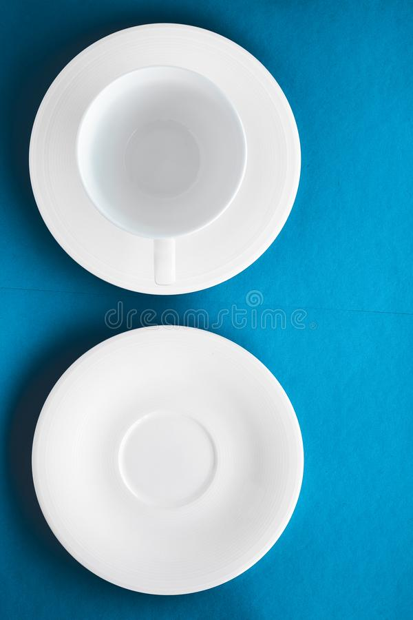 White tableware crockery set, empty cup on blue flatlay background. Kitchen, table decor and drinks menu concept - White tableware crockery set, empty cup on stock photography