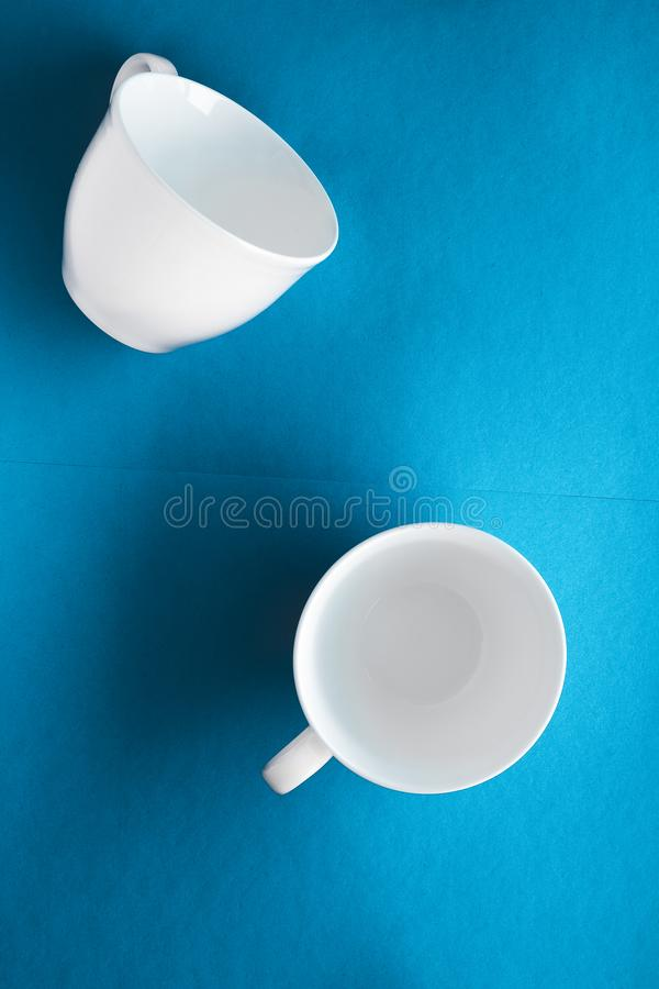White tableware crockery set, empty cup on blue flatlay background. Kitchen, table decor and drinks menu concept - White tableware crockery set, empty cup on royalty free stock image