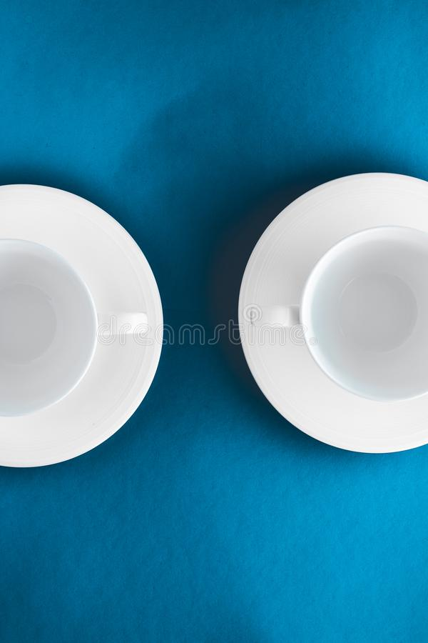 White tableware crockery set, empty cup on blue flatlay background. Kitchen, table decor and drinks menu concept - White tableware crockery set, empty cup on stock photos