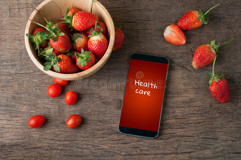 Kitchen table with fresh strawberry and health care text on screen smart phone , healthy eating and dieting food. Kitchen table with fresh strawberry and health stock images