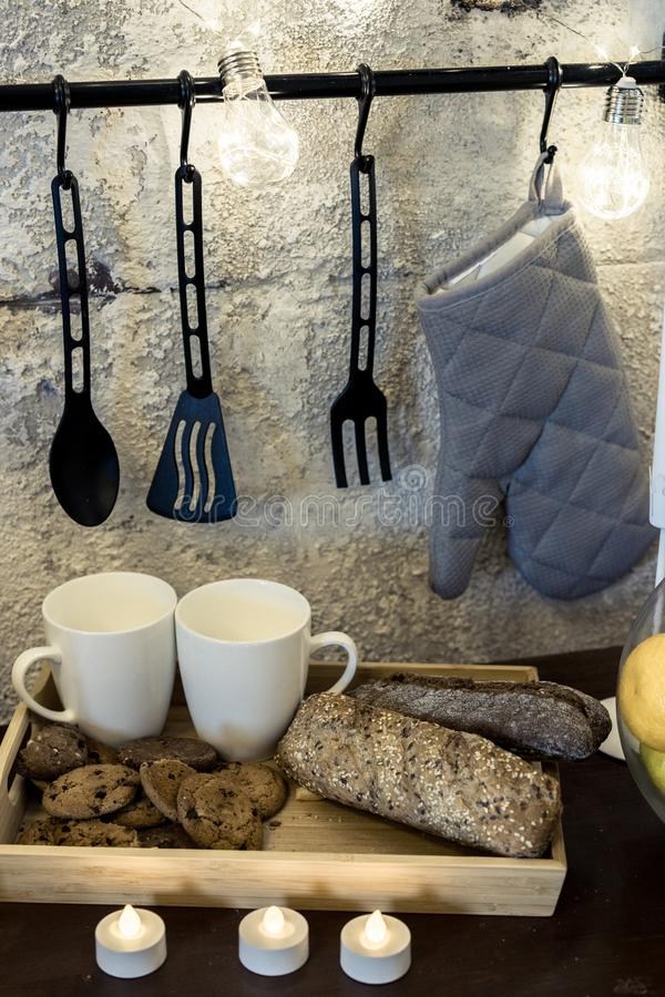 On the kitchen table in front of a concrete gray wall are white whistles a garland. hanging pot holder. waiting for valentine`s royalty free stock photo