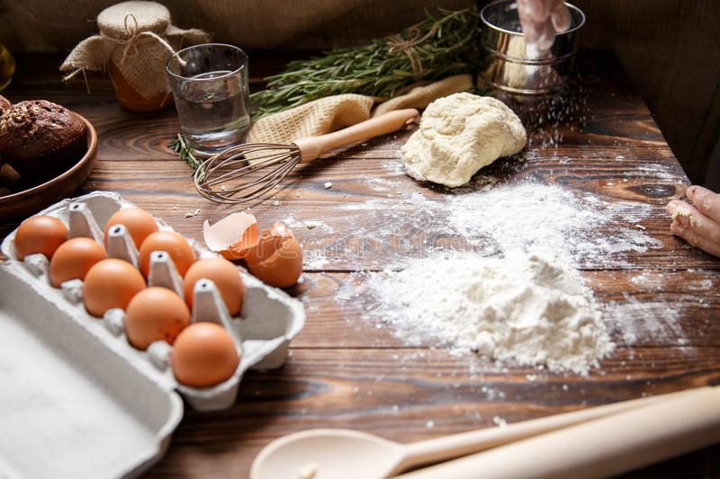 On the kitchen table, a ready-made dough, scattered flour and a tray with eggs. royalty free stock photo