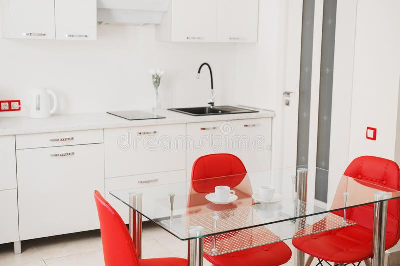 Kitchen table with red chairs. Modern apartment. Coffee cup on the table against the background of the kitchen. Luxury home. stock image