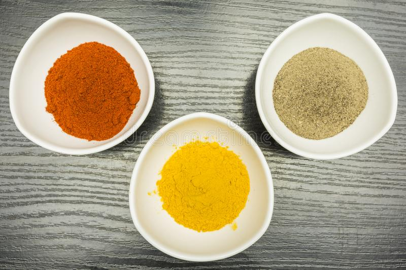 On the kitchen table, a set of three bowls with spices - pepper, paprika and curry.View from above. On the kitchen table a set of three bowls with spices royalty free stock photography