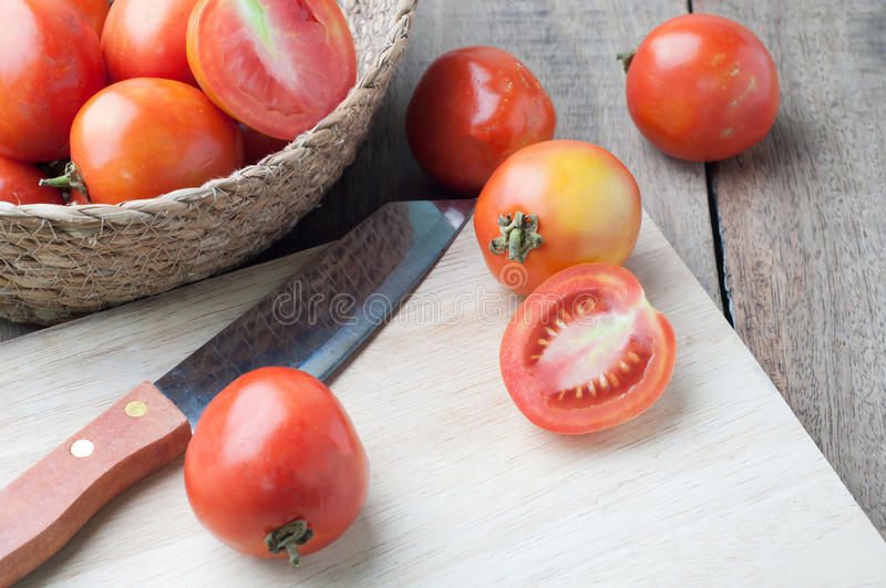Kitchen table with slice fresh tomatoes on wood basket. Kitchen table with slice fresh tomatoes on wood basket, selective focus on top view stock photos