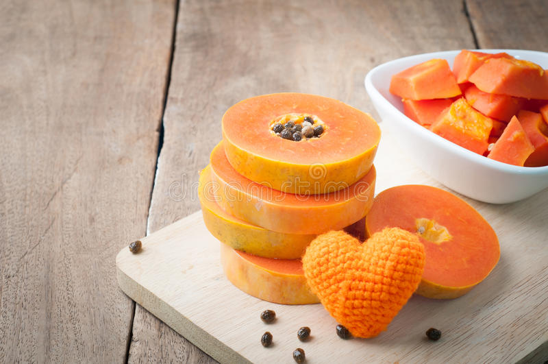 Kitchen table with stack layer slice fresh papaya, papaya and or. Ange heart shape on cutting board - healthy eating and dieting food, concept of health care royalty free stock photos